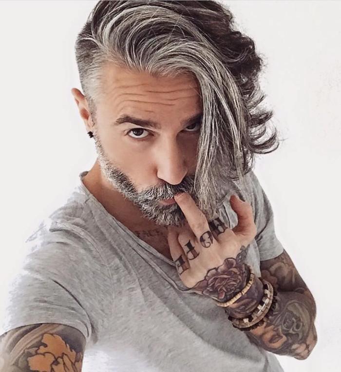 homme cheveux gris mi long avec coté court style coupe tendance hipster avec barbe poivre et sel