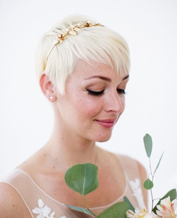 exemple de coloration blond polaire de coupe pixie avec frange asymétrique blonde et serre tête couronne dorée à motifs fleuris, bijou de cheveux élégant