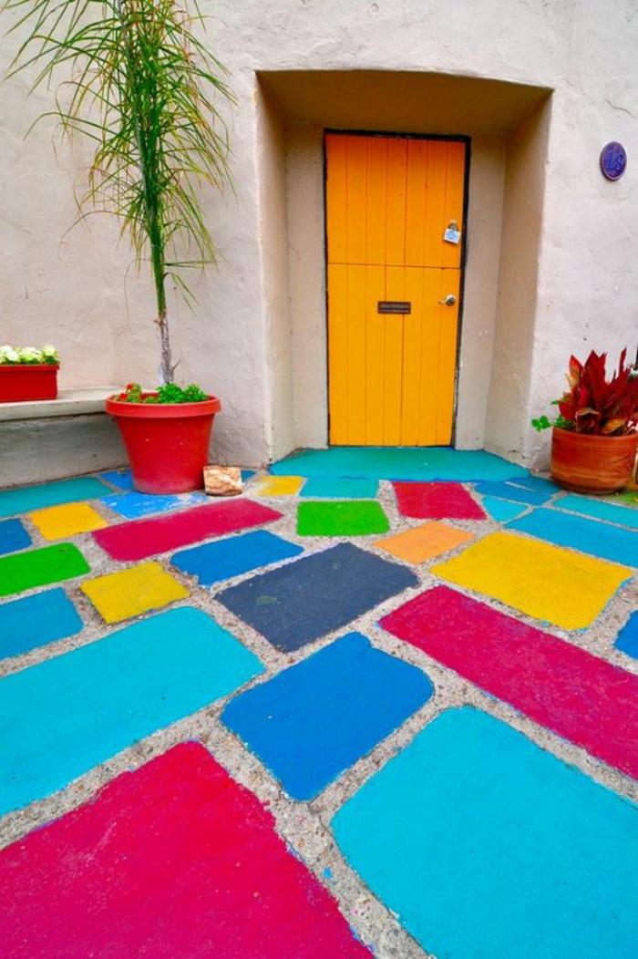 jardin paysager, amenagement exterieur, sol recouvertde dalles en couleurs vives et bleu pastel, porte orange, pot avec plante verte