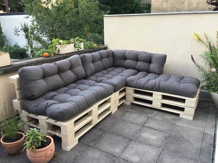 meuble avec palette en bois avec coussin d assise gris sur une terrasse couverte de dalles de béton, pots de fleurs