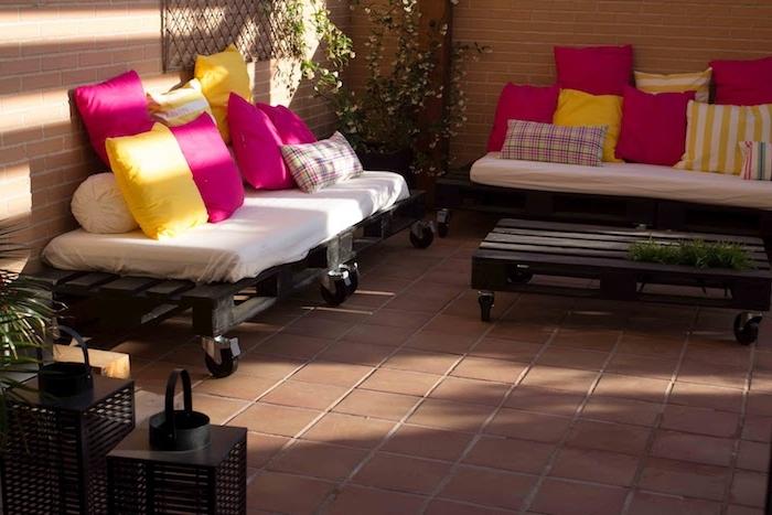 canapé en palette avec coussin d assise blanche, coussins décoratifs en rose et jaune et table palette basse
