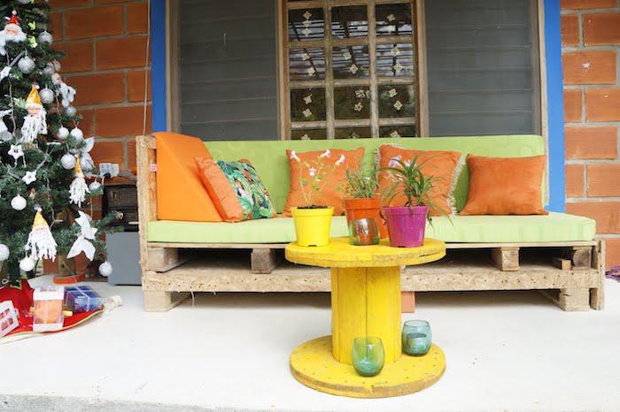 table en touret, coussin salon de jardin palette vert pistache et coussins décoratifs orange, touret jaune et pots de fleurs