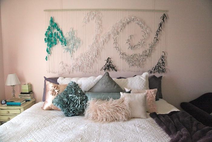 deco tete de lit en plumes vertes, blanches, noires, sur des fils blancs, coussins en vert, gris et rose, linge de lit blanc