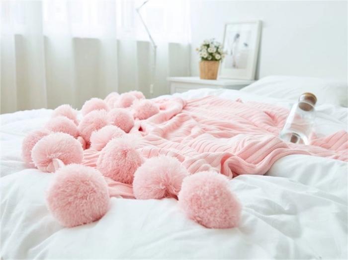 ambiance cocooning dans la chambre à coucher blanche avec modèle de plaid de couleur rose pastel décoré de grands pompons