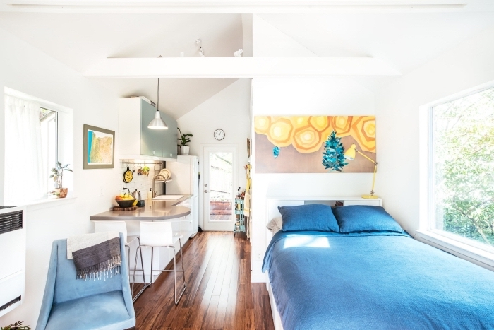 déco accueillante dans un petit studio avec cuisine d'angle et grand lit sous fenêtre, déco aux murs blancs et plancher de bois foncé