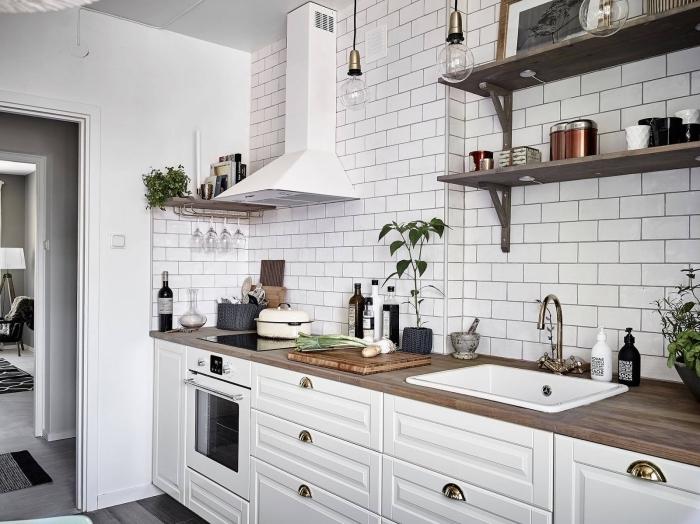 style industriel dans une cuisine campagnarde avec pan de mur en carrelage blanc et comptoir de bois foncé