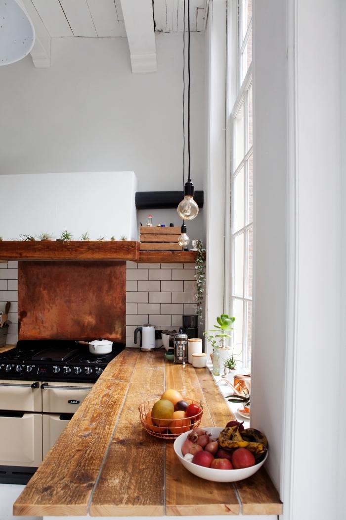 déco de style rustique dans une cuisine aux murs blancs avec plafond à poutres apparentes et crédence à carrelage briques blanches