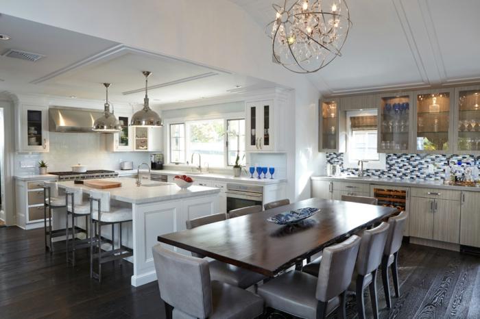 grande cuisine en couleurs claires, deux tables centrales de cuisine, sol boisé, plafond blanc