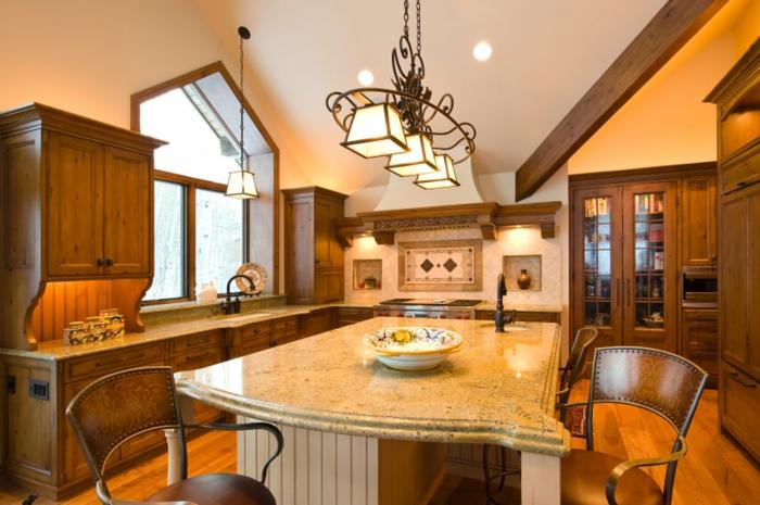 cuisine chaleureuse, îlot de cuisine chic avec comptoir en matériel luxueux, lampes vintage, cuisine en l