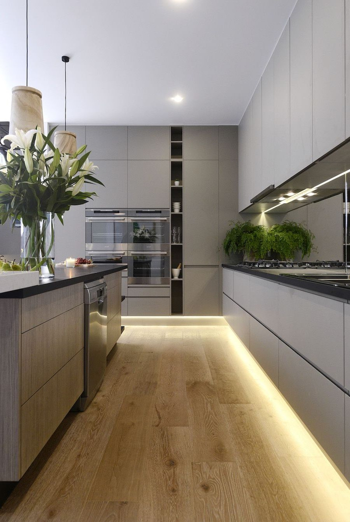 conception moderne d'une cuisine gris clair mat aux lignes épurées avec ses meubles sans poignées jusqu'au plafond
