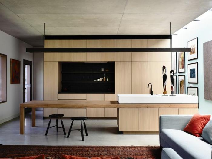 cuisine moderne en bois clair, sofa gris, ilot central simple et épuré, plafond en béton, cuisine design industriel