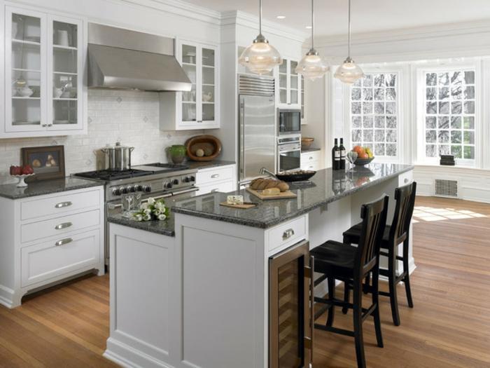 cuisine bois et blanc, cuisine avec ilot, ilot blanc comptoir noir, chaises noires traditionnelles, grandes fenêtres blanches