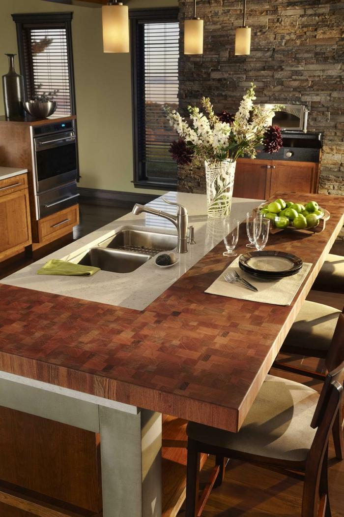 parement mural en pierre dans une cuisine moderne, table avec évier au centre de la cuisine, équipement en bois