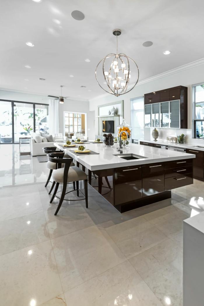cuisine spacieuse et en couleurs claires, grand chandelier, ilot en bois et blanc élégant, carrelage gris
