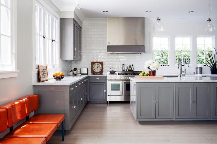 une cuisine blanche et grise lumineuse associant des meubles de cuisine gris mat aux comptoirs contrastant en blanc brillant et un mur de fausses briques blanches