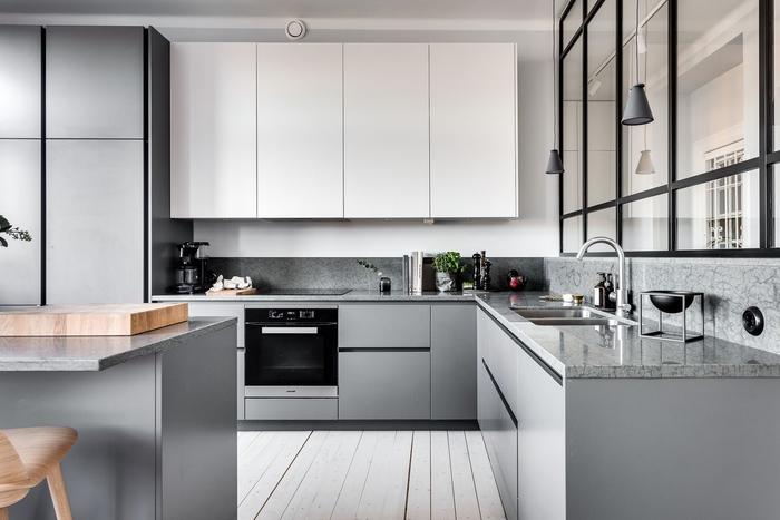 une cuisine blanche et grise au design épuré minimaliste qui associe simplicité et élégance grâce à quelques accents noirs