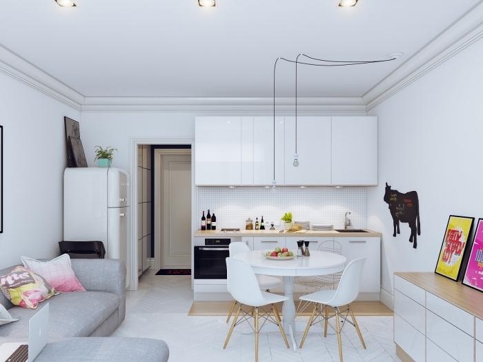 modèle de petite cuisine blanc et bois avec table ronde et chaises dans un studio aménagé avec coin canapé-lit