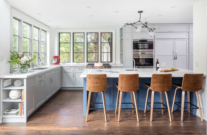 cuisine avec ilot bleu et blanc plein de charme avec des tabourets de bar en bois qui apportent une touche chaleureuse à l'espace
