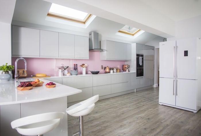 cuisine gris laqué lumineuse et douce associant des meubles de cuisine au design épuré à une crédence rose poudré à finition brillante