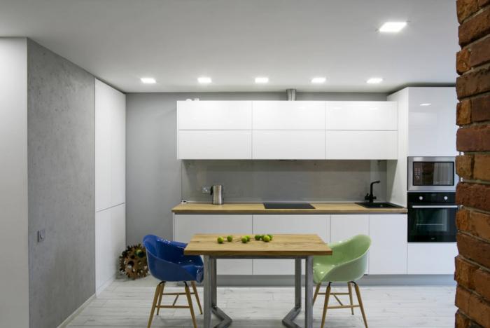 quelle couleur pour les murs d'une cuisine blanc laqué, design minimaliste et épurée d'une cuisine blanche laquée rehaussé par les murs gris et le comptoir en bois clair