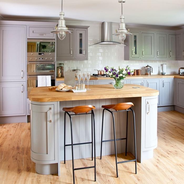 une cuisine grise et bois de style bistro qui associe des meubles gris et rose poudré avec un plan de travail en bois clair et un mur en fausses briques blanches