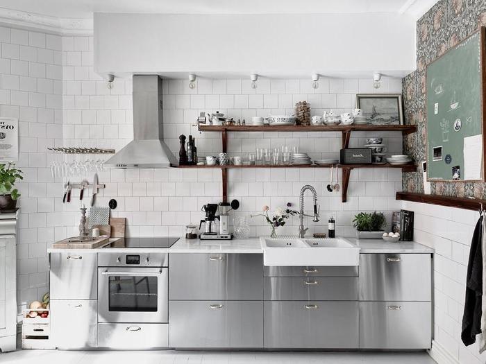 une cuisine grise et bois semi-industrielle entièrement en acier inoxydable associée à un carrelage mural blanc et des étagères en bois rustique