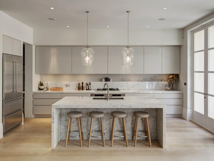 cuisine gris laqué aménagée en longueur et équipée d'un îlot en marbre tendance qui s'harmonise à l'ambiance monochrome élégante