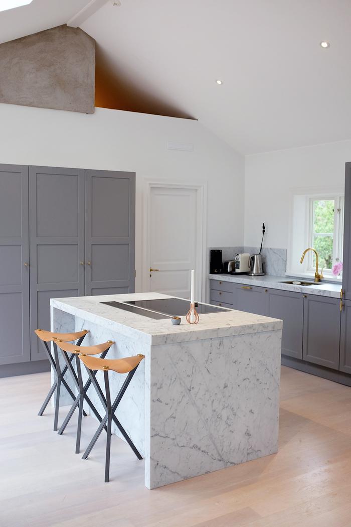 cuisine blanche et grise qui mise sur l'élégance épurée de son îlot central en marbre veiné en contraste avec les meubles de cuisine de style campagne
