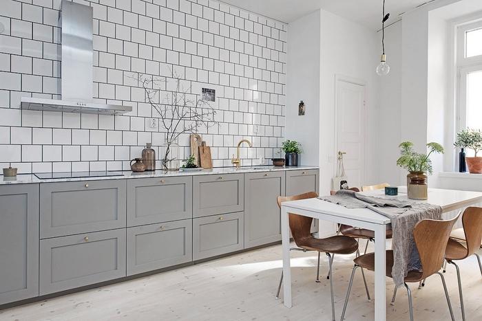 quelle couleur pour une cuisine d'ambiance nordique, design simple et épuré d'une cuisine grise sans meubles hauts qui affiche un joli carrelage mural blanc