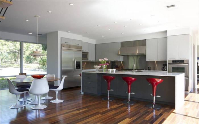 des tabourets de bar rouge brillant qui apportent une touche de couleur dans la cuisine grise et rouge contemporaine