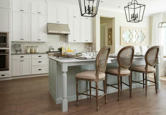ilot centrale de cuisine, chaises élégantes, îlot bleu, sol en bois, cabinets blancs suspendus
