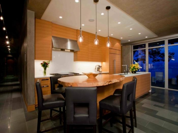 cuisine avec ilot central, table en bois naturel, ilot rectangulaire, chaises noires, lampes suspendues