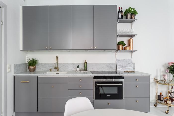 cuisine grise moderne et minimaliste qui associent des meubles de cuisine gris mat aux poignées dorées et à un comptoir en marbre pour une allure chic et contemporaine
