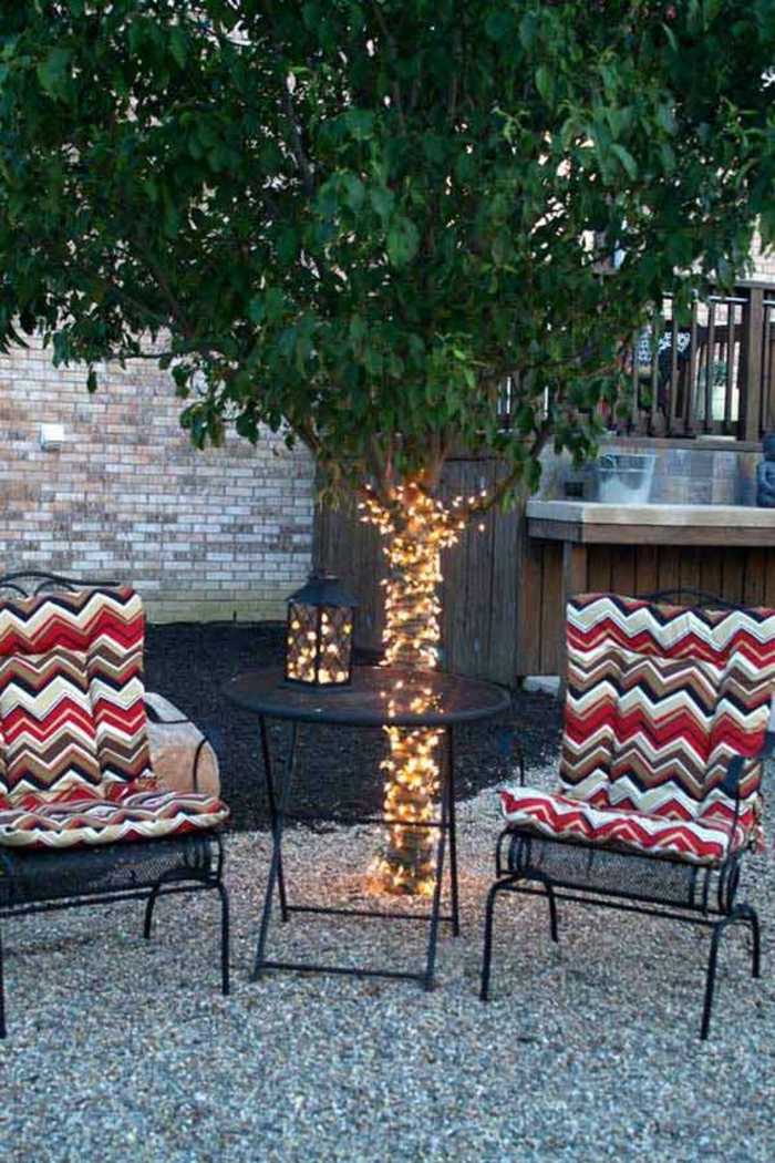 amenagement exterieur, décorer son jardin, déco jardin récup, arbre avec le tronc enveloppé de guirlande lumineuse, deux fauteuils en métal noir avec des coussins aux motifs graphiques en rouge, blanc et noir