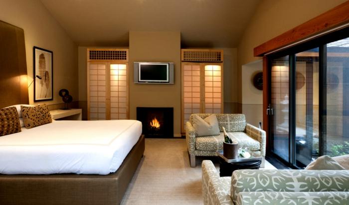 déco de chambre feng shui, lit plateforme en cuir, cheminée murale, fauteuils en textile