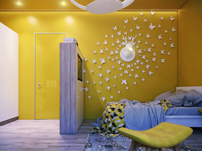 une chambre d'enfant aux murs et plafond peints en jaune brillant, sol recouvert de parquet gris, applications de papillons en carton blanc qui tournent autour d'une applique murale, déco murale, luminaire blanc au plafond en forme de disque