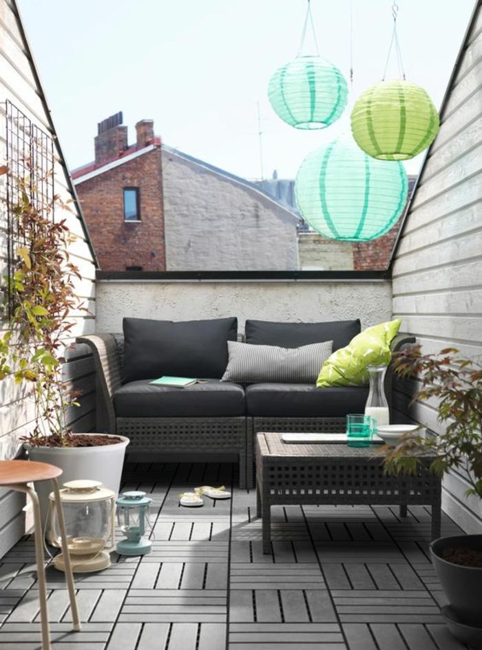 idee amenagement terrasse avec des meubles en rotin et des coussins noirs, table rectangulaire basse avec des ornements orientaux, lame bois au sol, lanternes en carton en vert réséda et bleu pastel suspendus au plafond