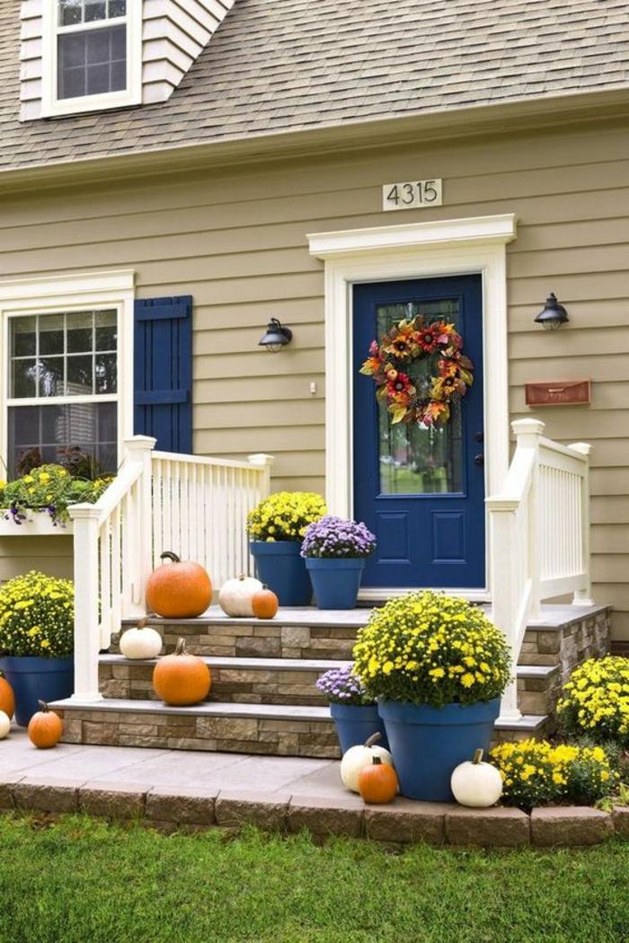 idee amenagement jardin devant maison, jardin deco, maison peinte en beige, cadre porte accentué avec du blanc, porte en bleu canard, escalier décoré avec des citrouilles de couleur et taille différente
