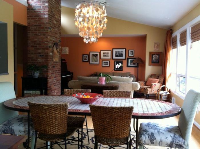 grande table ovale, chaises tressées, plafonnier impressionnant, peinture murale jaune et orange, peinture tendance salon