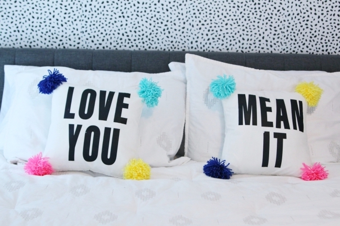 comment aménager une chambre romantique à deux, modèle de housse à imprimés avec déco en pompons de couleurs vibrantes