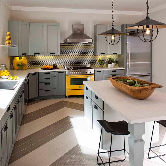 cuisine gris clair égayée par des accents jaunes sur la crédence à motif graphique ou dans la déco
