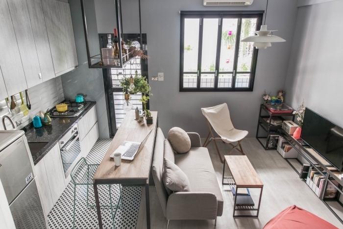 design intérieur cozy dans un studio avec petite cuisine et salon aménagé avec meubles fonctions de bois clair