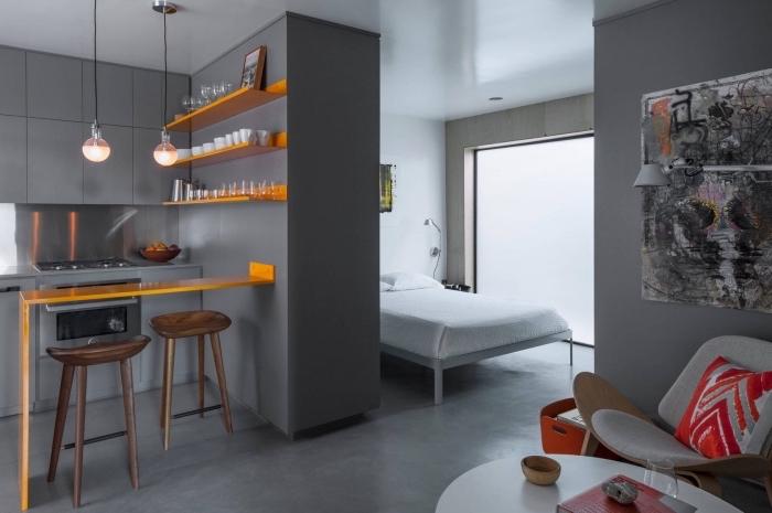 exemple séparation pièce dans un studio avec muret gris entre la cuisine grise et la chambre à coucher blanche