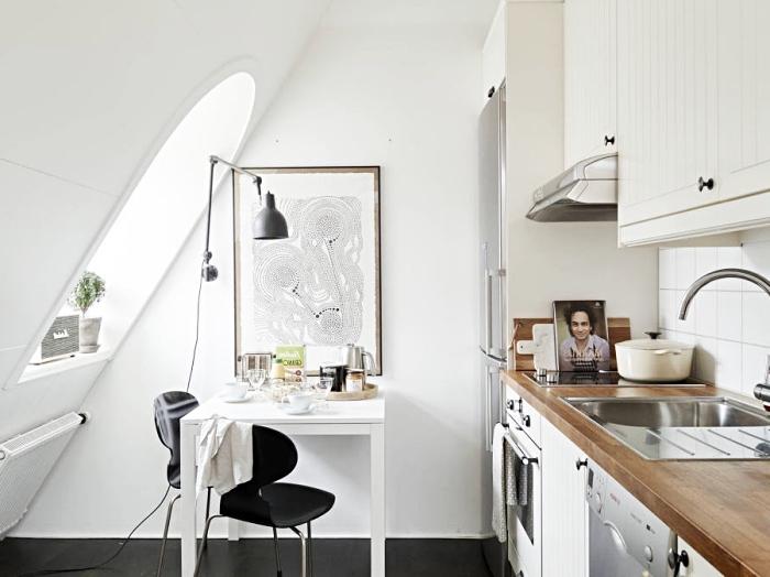 idée aménagement de petite cuisine sous pente avec table à manger blanche et chaises noires, cuisine bien équipée aux comptoirs de bois massif foncé