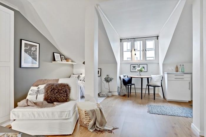 meubles fonctionnels pour aménagement sous pente dans un petite studio aux murs blancs avec pan de mur gris et plancher de bois stratifié