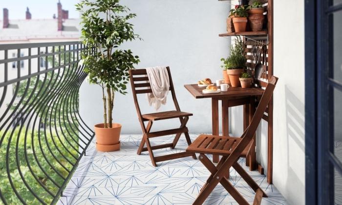 aménagement de petite terrasse ou balcon avec garde-corps en fer forgé et mobilier de jardin en bois foncé