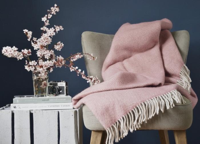 objets de décoration d'intérieur de style cozy avec une chaise grise et plaid rose pastel à franges blanches