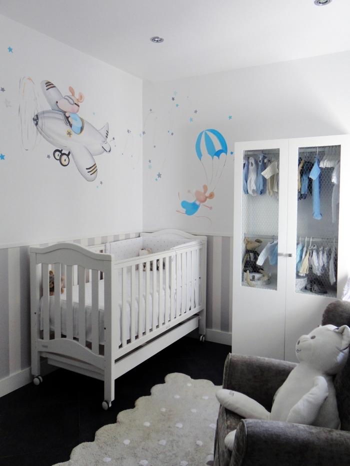 intérieur dans une pièce nouveau-né sur le thème aventure avec murs blancs à dessins animaux et plancher noir