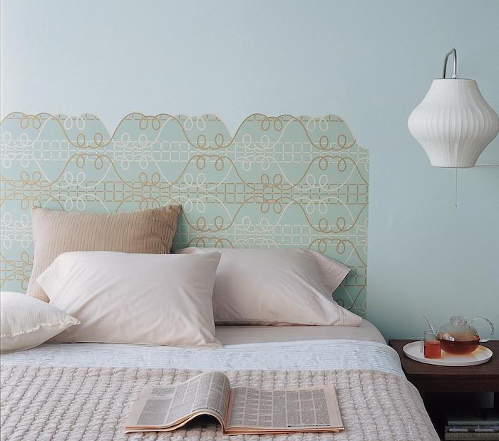 idée de tête de lit papier peint en bleu et beige sur un mur bleu, linge de lit rose et blanc, table de nuit bois, lampe blanche