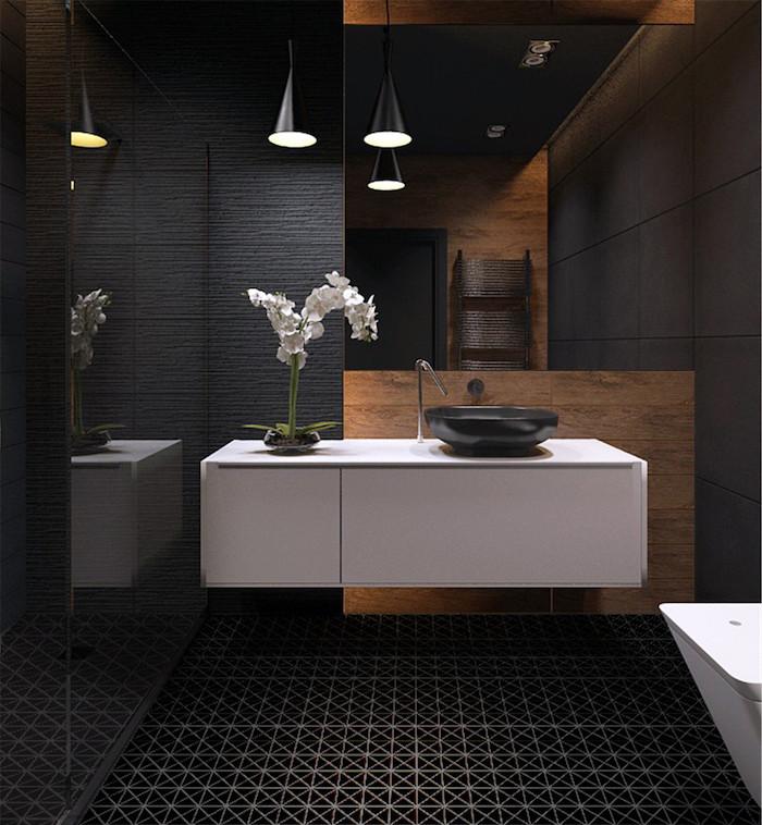 salle de bain moderne à déco noire et bois avec carrelage noir design et meuble lavabo blanc suspendu